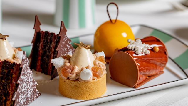 Sweet treats on a plate, as part of Claridge's Festive Afternoon Tea. These include two Christmas tree-shaped chocolate cakes, a small tartlet, yellow edible bauble and a red yule log.