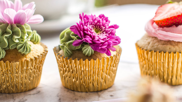 Three colourful cupcakes covered in icing, fruit and flowers