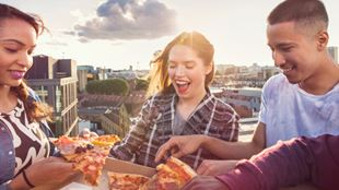 Three people are smiling as they reach for slices of pizza.