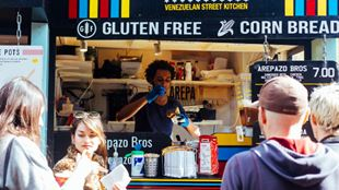 A man in a food truck is serving food to customers standing outside.