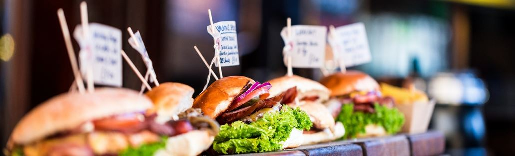 Tasty and well-filled burgers lined up on a wooden presentation tray with labels so customers can pick which one they want to order.