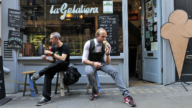 Two men eating ice cream outside an ice cream parlour