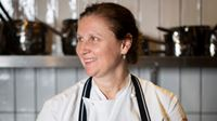 Angela Hartnett is posing for the camera in a tiled kitchen, with pan and pots on shelves in the background.