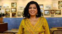 Asma Khan is smiling and posing for a portrait in her restaurant.