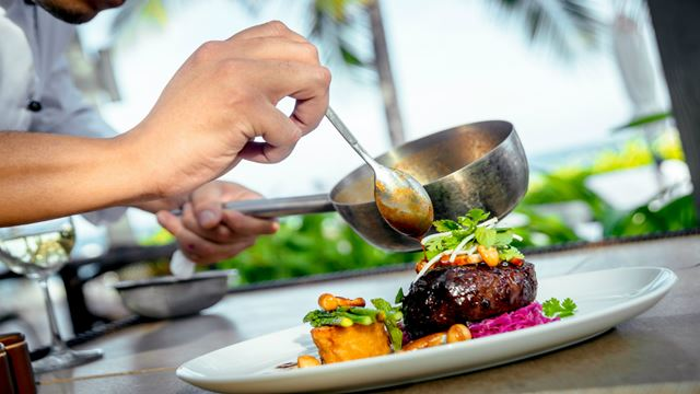 A chef adds sauce to a colourful dish on a white plate.