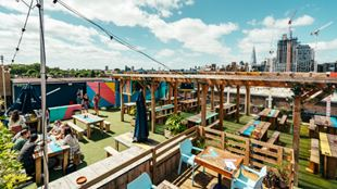 Panoramic shot of benches and seating areas on the roof of Skylight bar with London cityscape on horizon.