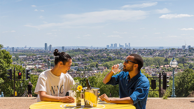 Two people with drinks sit on a yellow picnic-style table on a sunny day, with London's skyline behind.