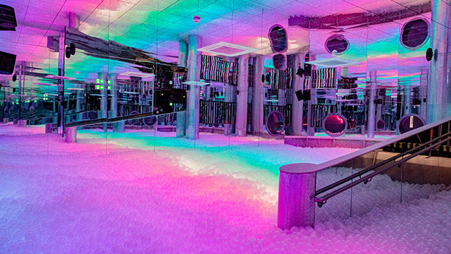A mirrored room with a rainbow ball pit