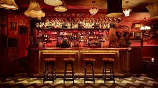 The 1920s Chicago-inspired bar, complete with red velvet bar stools and retro lampshades, at Barts in London.