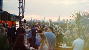 A busy rooftop bar with fairy lights and stunning views across London's skyline.