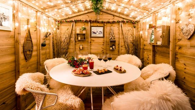 The inside of a wooden chalet at Lodge d'Argent, with fur-covered chairs, cocktails, drinks and small plates of food on a table, and lit fairy lights.