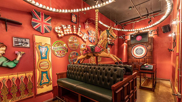 A Victorian-inspired fairground horse in front of a dart board inside Flight Club