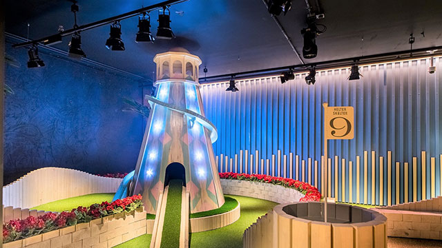 A flag at hole nine next to an illuminated helter skelter golf obstacle at Swingers West End.
