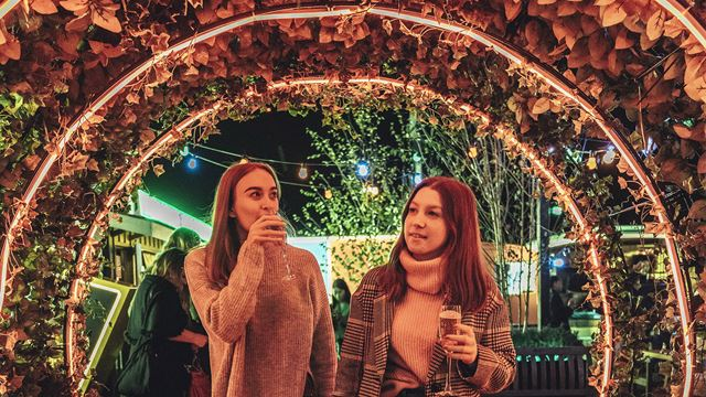 Two women sip on champagne underneath an arch of foliage at John Lewis & Partners' rooftop bar.
