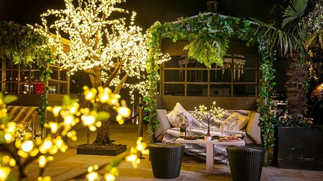 A view of Madison's Enchanted Woods winter terrace, with illuminated fairy lights around trees and a table with a bottle and glasses of champagne.