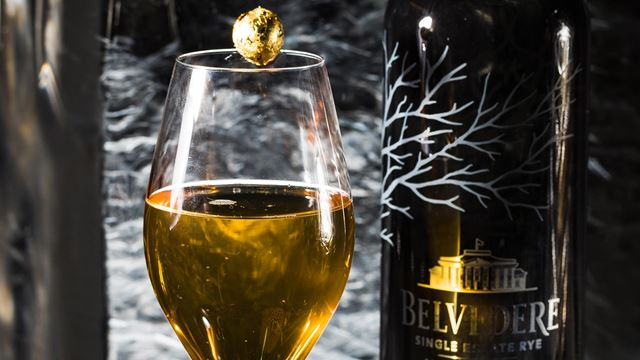 A cocktail glass is filled with the yellowish Belevedere + Ice cocktail, with a gold leaf ball balanced on top, and a bottle of Belvedere vodka in the background.