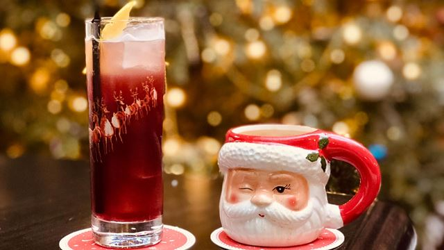A ruby-red-coloured cocktail topped with a slice of lemon stands next to mug with a winking Santa face.