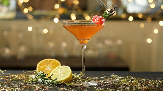 An orange-coloured Christmas Kiss cocktail, featuring cranberries and a smoking sprig of rosemary as garnish.