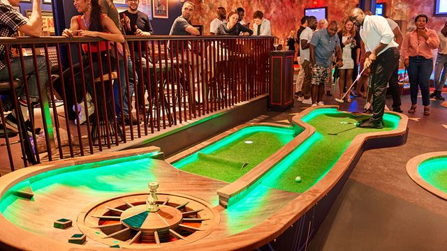 A man takes a putt on one of Puttshack's brightly lit mini golf holes, while people look on.