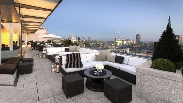 An empty terrace with lounge-style seating and London's skyline in the background, at dusk.