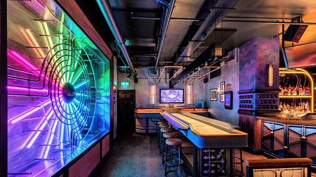 An interactive shuffleboard next to a multi-coloured light