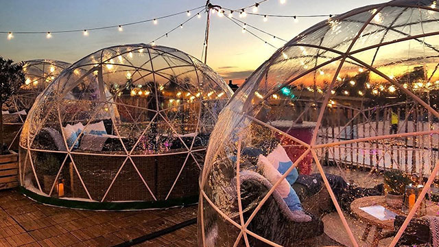 "Two transparent geometric ""igloos"", one in the foreground and one in the background, complete with tables, seating and cushions. Outside, it's dusk and chains of lights are illuminated."