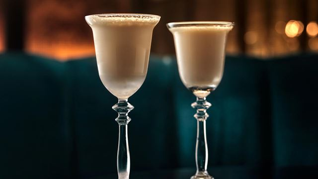 Two tall cocktail glasses, filled with the light-brown-coloured St James Bar's Milky Cat cocktail, against a dark background with lights.