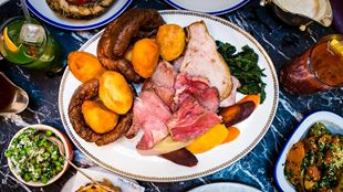 A roast dinner on a large plate, surrounding by side plates of vegetables, taken from above.
