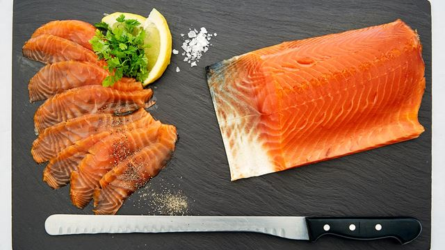 A pink tranche of smoked salmon lays on a slate platter, with slices of smoked salmon and lemon alongside.