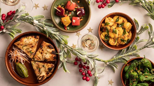 Four plates of food from the festive menu at Cinnamon Kitchen City sit on a table decorated with frosted foliage and stars.