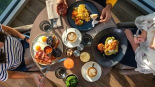 An aerial image of three people having brunch, including a full English, avocado on toast, scrambled eggs and coffee.