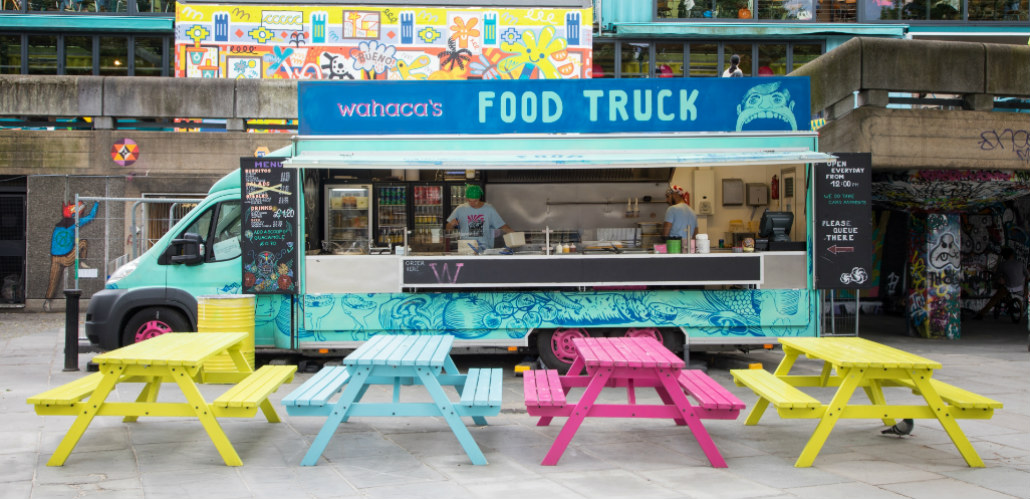 Colourful picnic benches in front of food truck on South Bank, London.