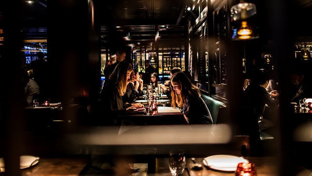 Diners eating behind wooden panel at Hakkasan Mayfair restaurant