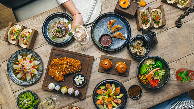 Multiple plates of food, on a table, take from above.
