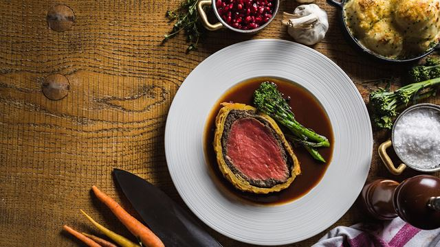 The Kitchens' beef Wellington, served rare, and long-stemmed broccoli sit on a plate with a dark red wine reduction sauce. The plate rests on a wooden surface surrounded by raw ingredients such as carrots, pomegranate and carrots.