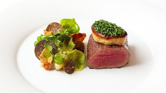 A fillet of venison, cooked pink, sits alongside a salad including black truffle at Pétrus.