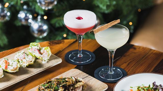 One pink and one cream cocktail, plus three small plates of food on a table, with a Christmas tree in the background.