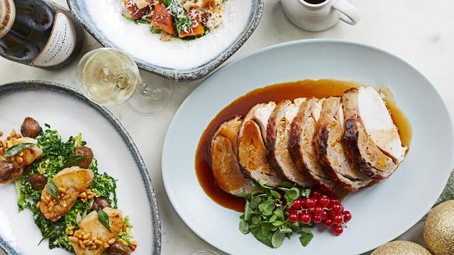 Sliced turkey breast sits on a plate with gravy and redcurrants, alongside two plates of vegetables and a glass and bottle of wine., at Sea Containers London.