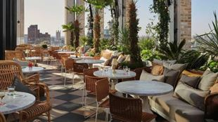 Rooftop terrace restaurant with chairs and tables set out or dining, with London skyline in distance.