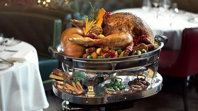 A golden roast turkey sits on the top tier of a two-tiered silver platter, surrounded by garlic, redcurrants, pigs in blankets and vegetables, at Simpson's in the Strand. The bottom tier includes brussels sprouts and chestnuts.