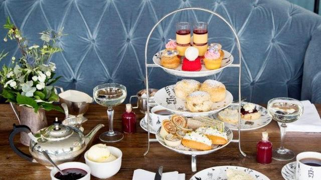 A selection of cakes, scones and sandwiches on a stand served with tea