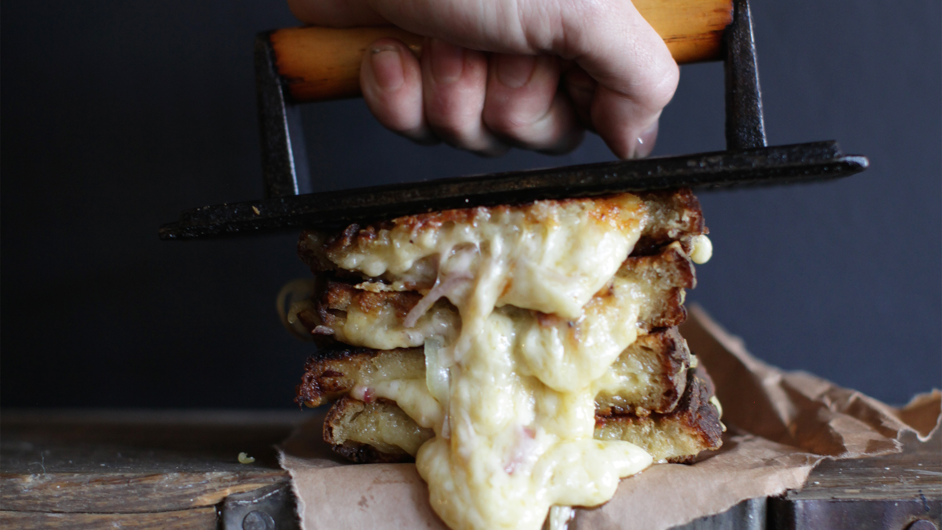 A toasted sandwich with cheese oozing out is squashed by The Cheese Truck's chef holding an iron press. Image courtesy of The Cheese Truck.