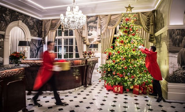 A butler, dressed in a red coat and black trousers, decorates a Christmas tree in the lobby at The Goring, featuring a chandelier and black and white-tiled floor. Another butler walks past, carrying a present.