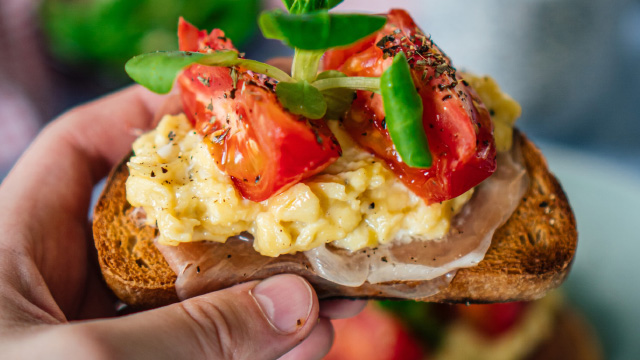 Scrambled eggs with tomatoes and ham on toast for a traditional brunch