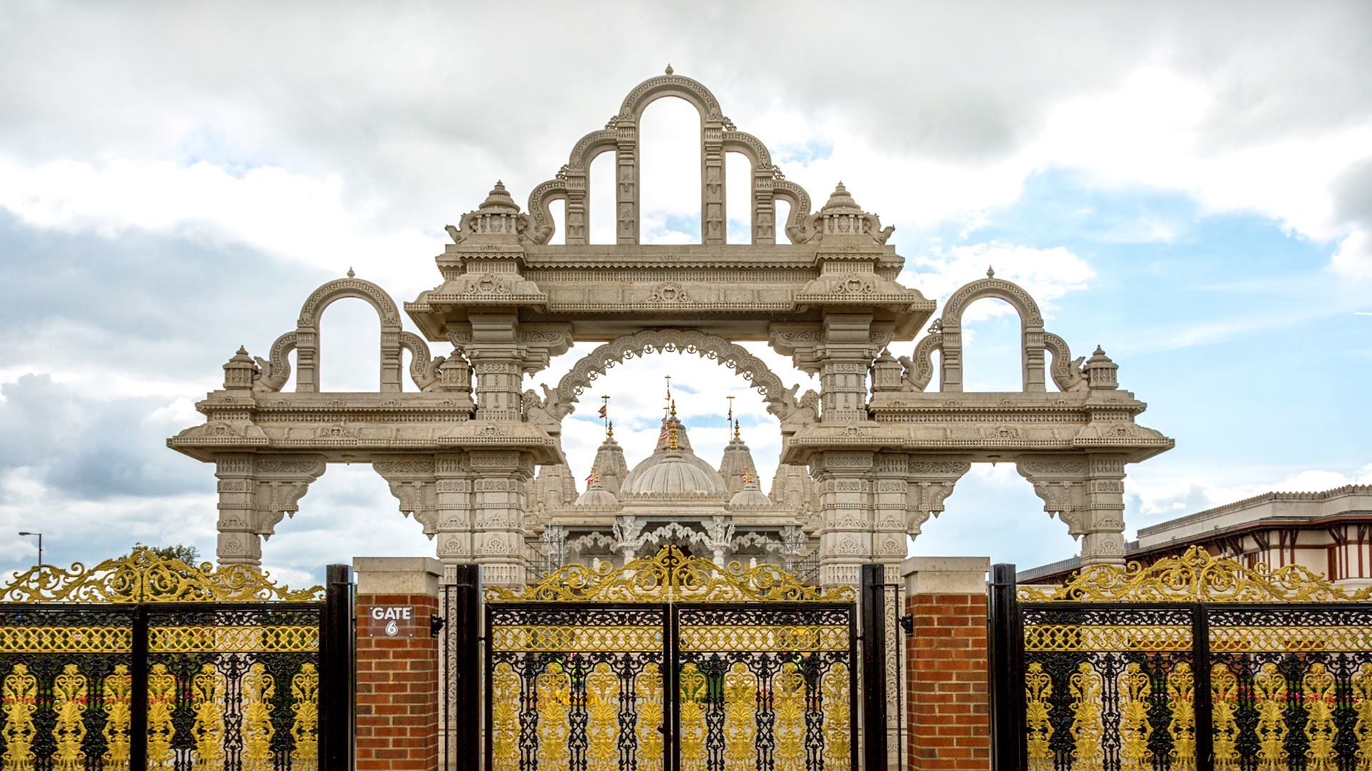 Golden gates in front of Neasdon Temple with a cloudy sky overhead