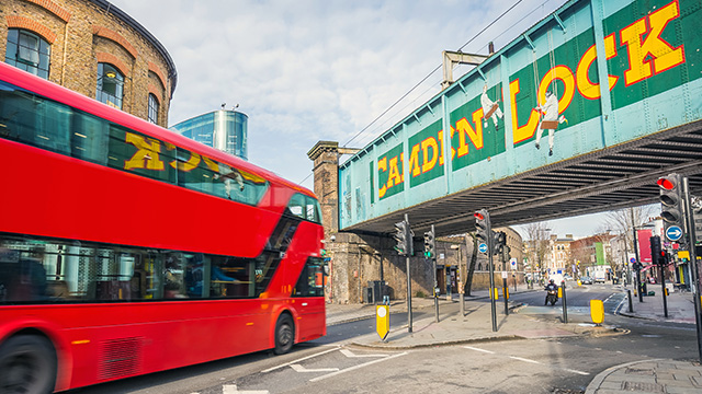 Big red double-decker London bus driving under bridge with Camden Lock painted on it