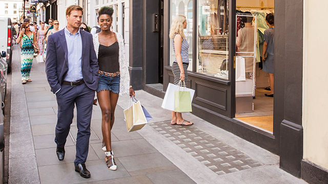 A man and women stroll along a street with shopping bags in hand, while another woman looks in a shop window.