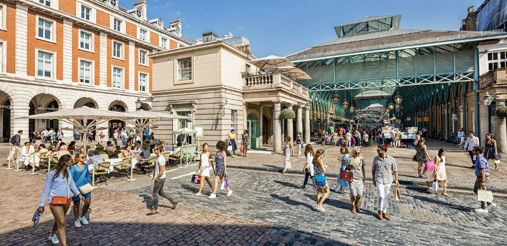 Shoppers walk around Covent Garden's West Piazza, in front of the market building, on a bright, cloudless day.