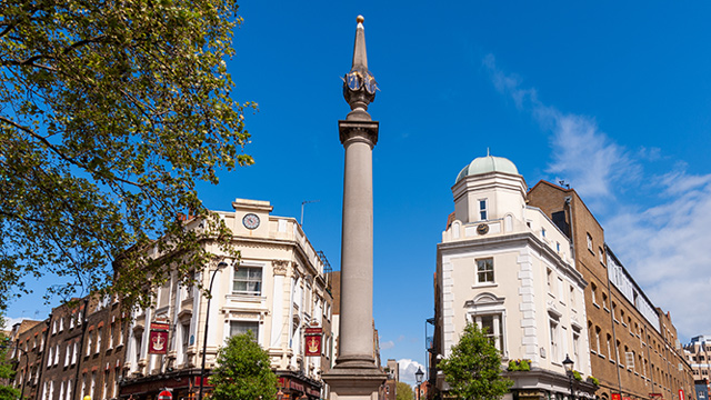 Seven Dials monument centred with buildings either side and bright blue sky above