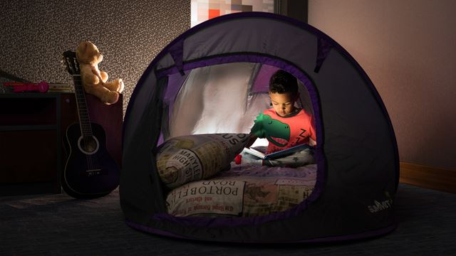 Little boy sitting inside a dome shaped tent within a room reading by torch light